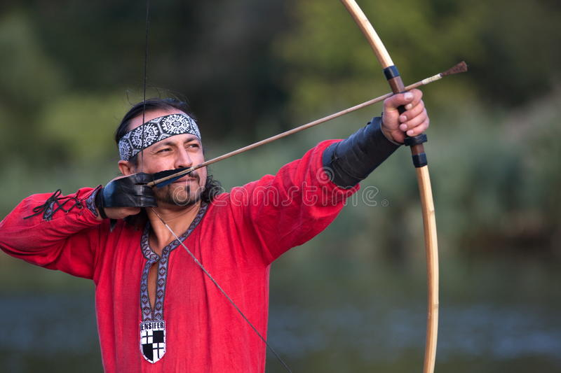 Archer pulls on the string. Man in medieval dress aims a bow stock photography