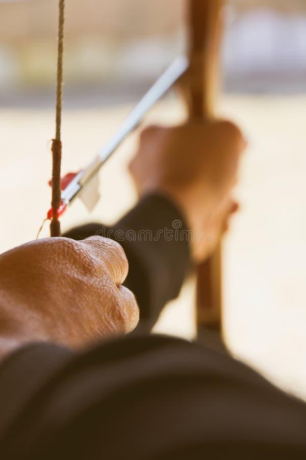 Archer rymmer hans pilbåge som siktar på ett mål royaltyfria foton