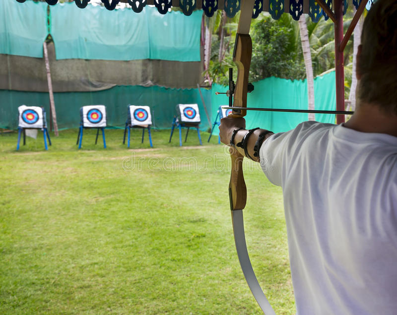 Archer takes aim at a target. Archer man pulls the bowstring and arrow, aiming at a target royalty free stock photo