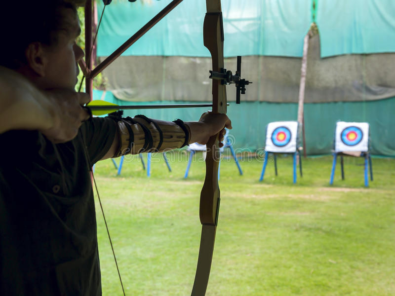 Archer takes aim at a target. Archer man pulls the bowstring and arrow, aiming at a target royalty free stock photos