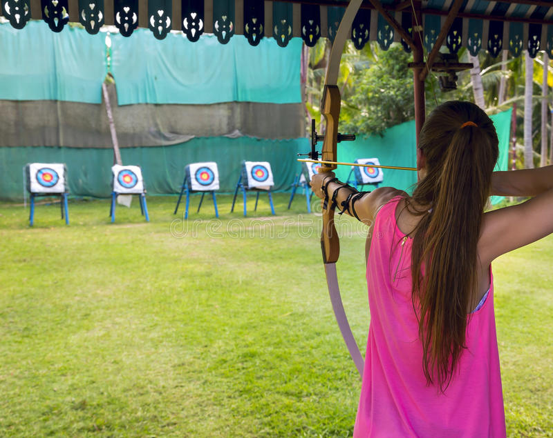 Archer takes aim at a target. Archer young woman pulls the bowstring and arrow, aiming at a target royalty free stock photography