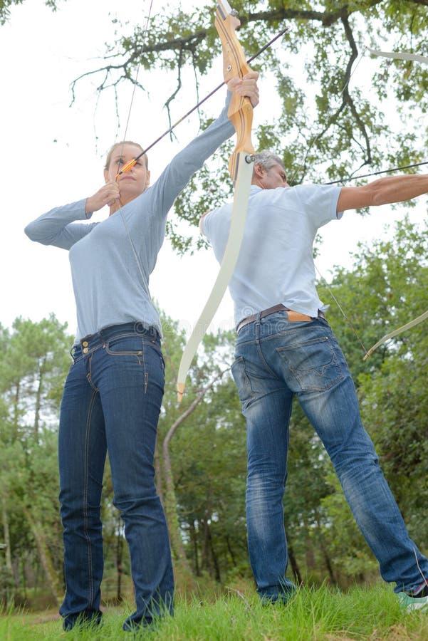 Archery человека и женщины практикуя стоковые фотографии rf