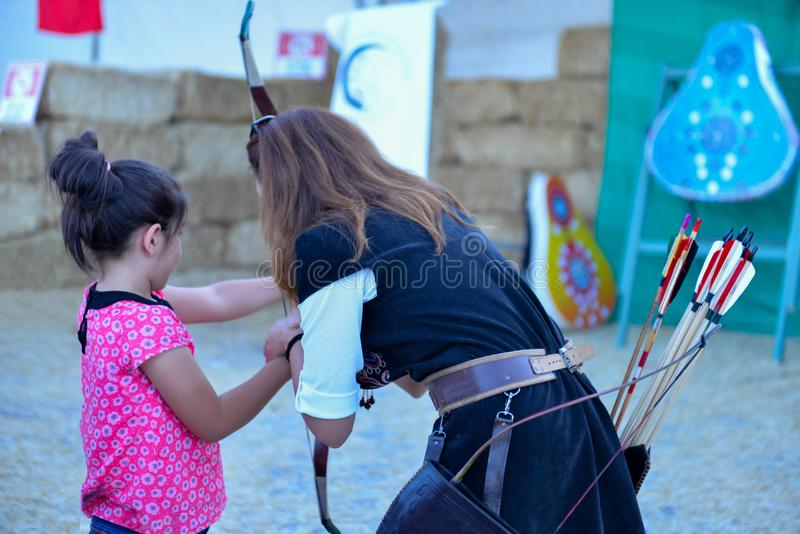 Archery trainings, shots and traditional local outfits. Archer trainer and archery knowledge and skill royalty free stock images