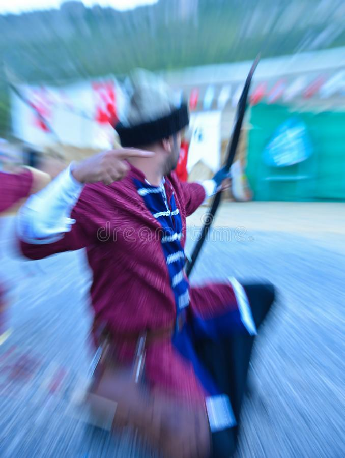 Archery trainings, shots and traditional local outfits. Arrow moment of the professional Archer royalty free stock photos