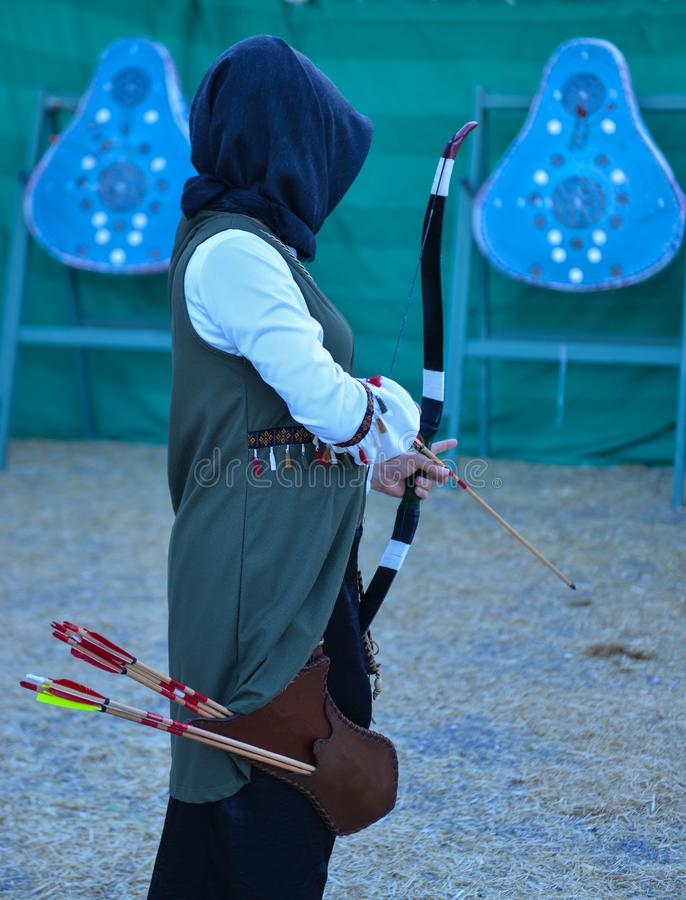 Archery trainings, shots and traditional local outfits. Moment of female professional archer stock image