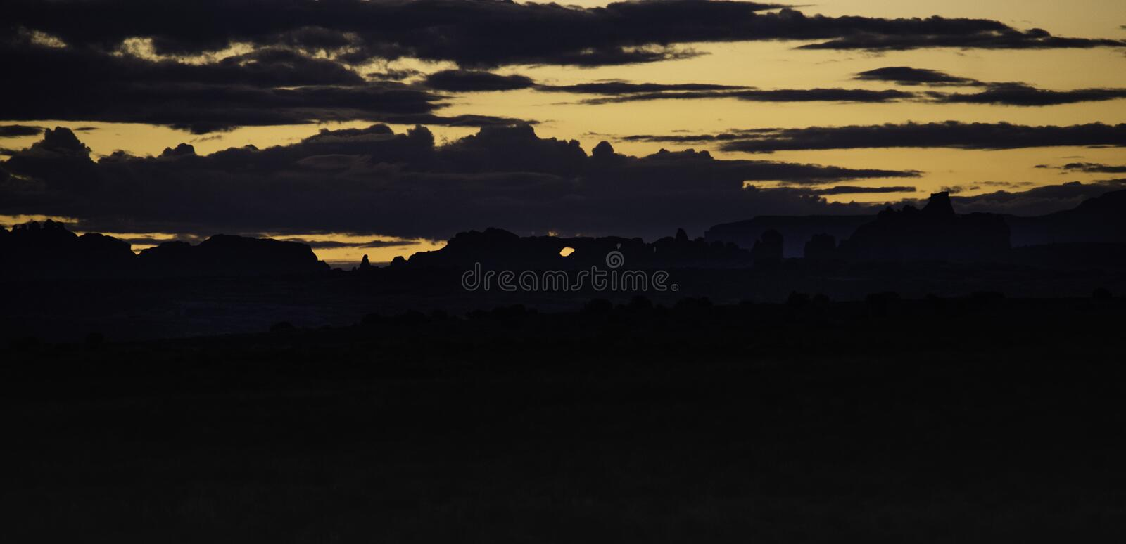 Arches National Park at sunrise. Arches National Park, UT, sun rising over the desert mountains royalty free stock image