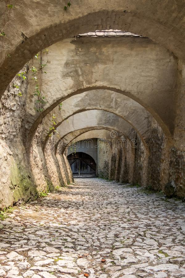 Arches over the cobblestone entrance to the Saxon UNESCO World Heritage Site of Biertan Fortified Church. Sibiu County, Romania. The Biertan fortified church is stock photography