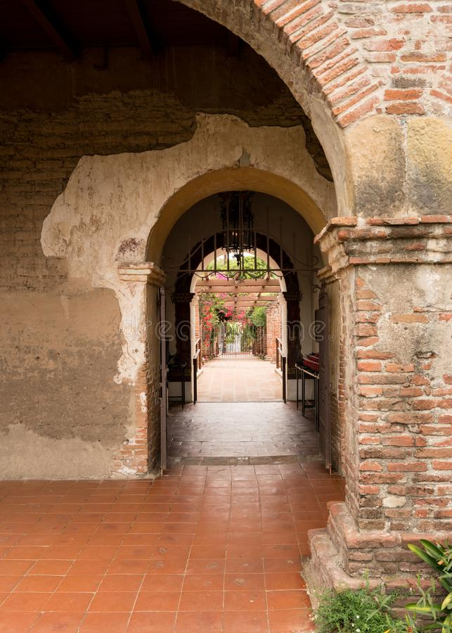 Arches and pathway in San Juan Capistrano mission royalty free stock photography