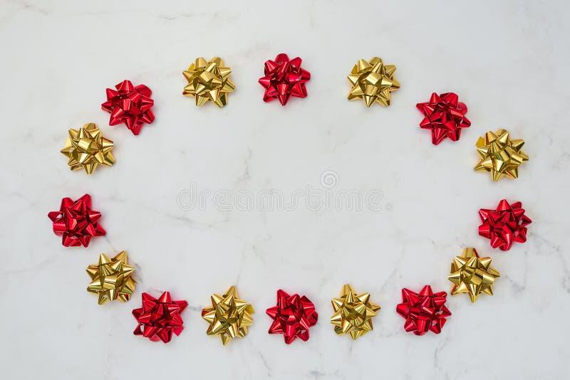 Archi festivi dell'oro e rossi su fondo di marmo bianco Contesto per le carte, inviti, saluti immagini stock libere da diritti