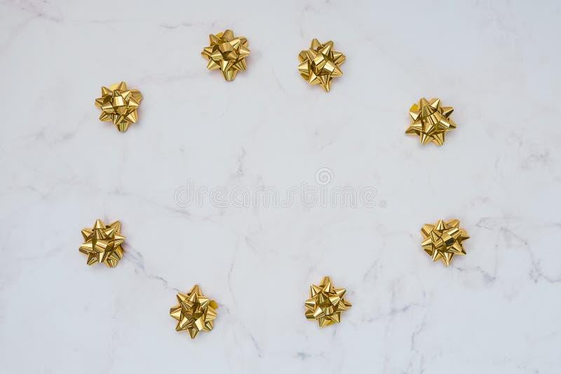 Archi festivi dell'oro su fondo di marmo bianco Contesto per le carte, inviti, saluti fotografie stock
