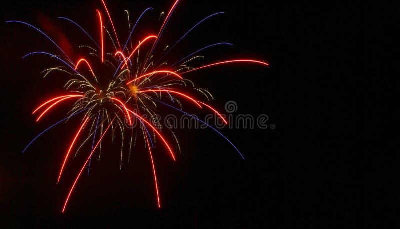 Archi rossi e blu con gli archi dell'oro in fuoco d'artificio concentrare durante il quarto di luglio immagini stock libere da diritti