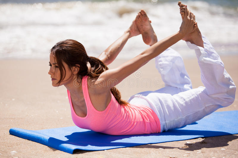 Arching back and holding feet. Cute Hispanic brunette arching her back and holding her feet from behind in a yoga pose at the beach royalty free stock photography