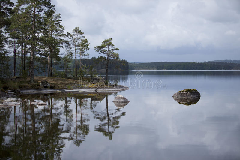 Archipelago. On a Cloudy evening an island in the Swedish archipelago casting a beautiful reflection in the shallow waters royalty free stock photo