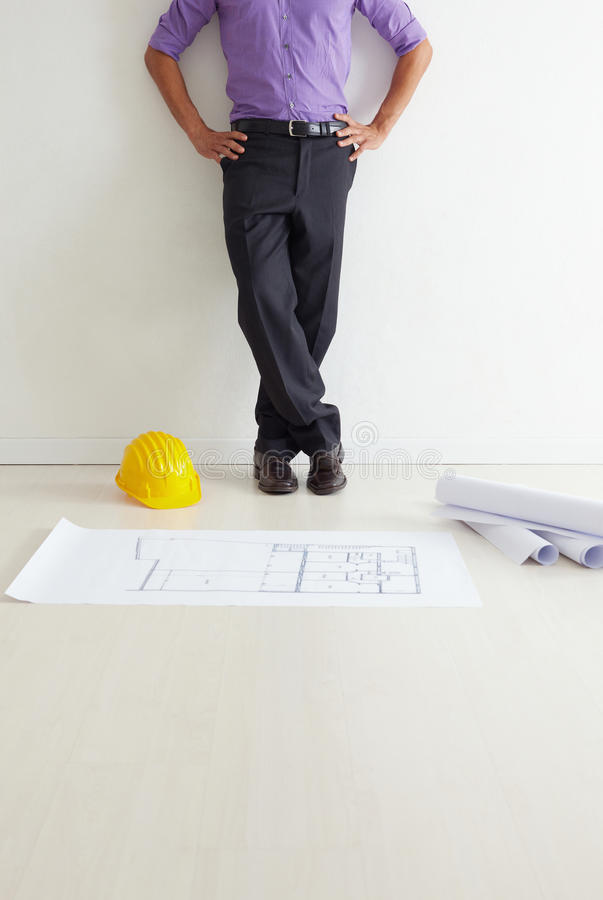 Architect. Cropped view of mid adult architect leaning on wall and blueprints on floor. Copy space royalty free stock image