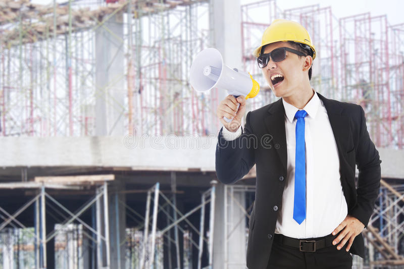 Architect announcing. Asian architect yelling through a megaphone shot at workplace outdoor royalty free stock photo