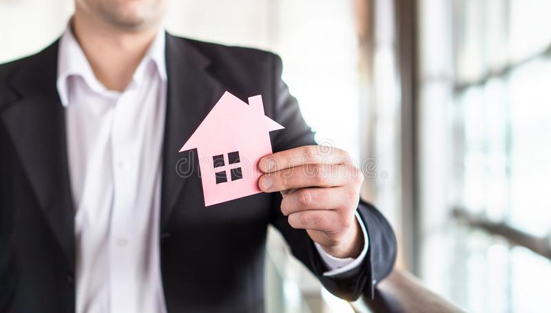 Architect, banker, realtor, agent, businessman or broker. Architect, banker, realtor, agent, businessman or broker holding paper house. Real estate or royalty free stock photography