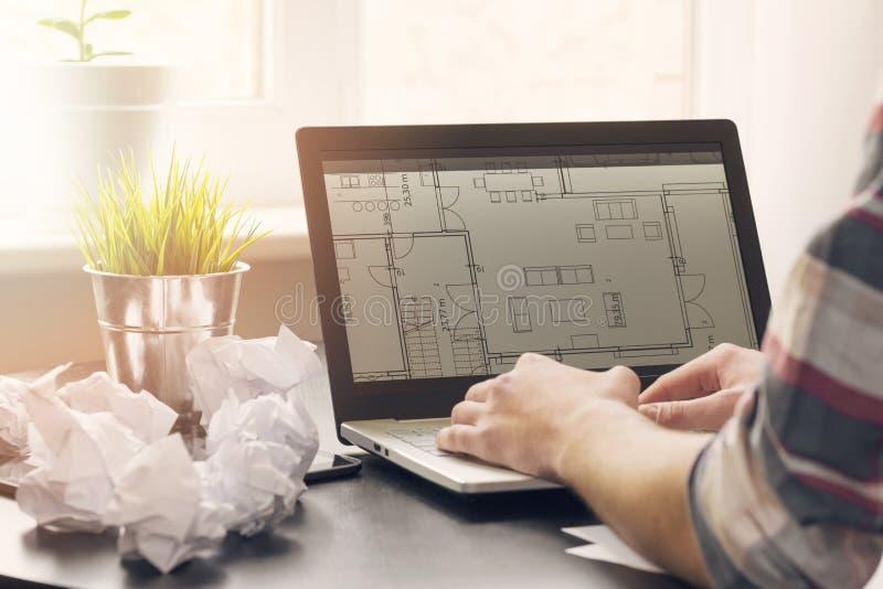 Architect, binnenlandse ontwerper die aan laptop met vloerplannen werken royalty-vrije stock foto's