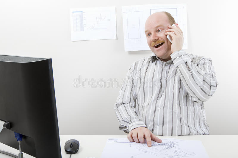 Architect With Blueprint Using Mobile Phone At Desk stock photos