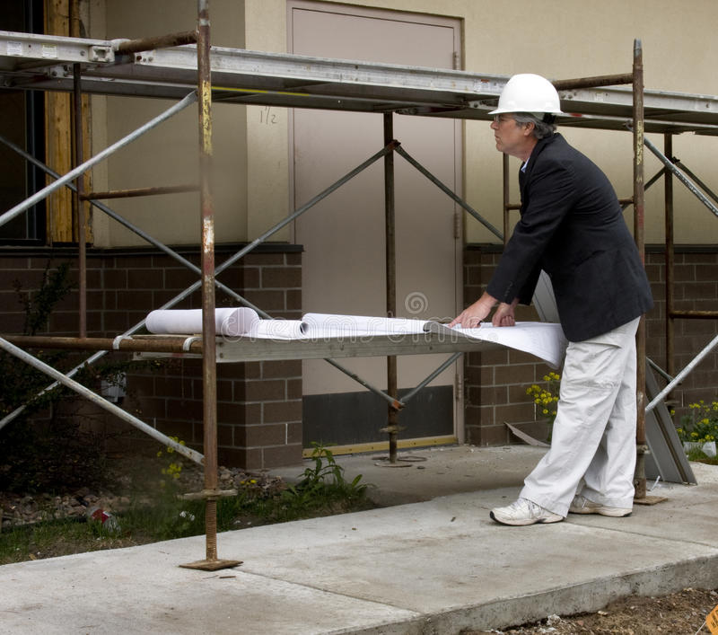 Architect with blueprints. At a construction job stock photos