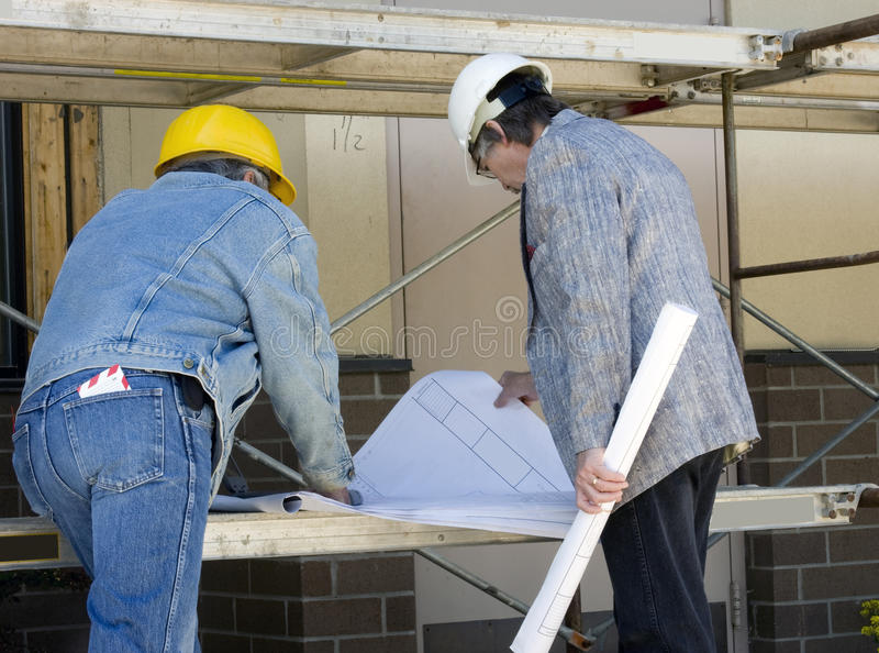 Architect and builder. Construction builder and Architect review blue prints at job site stock images