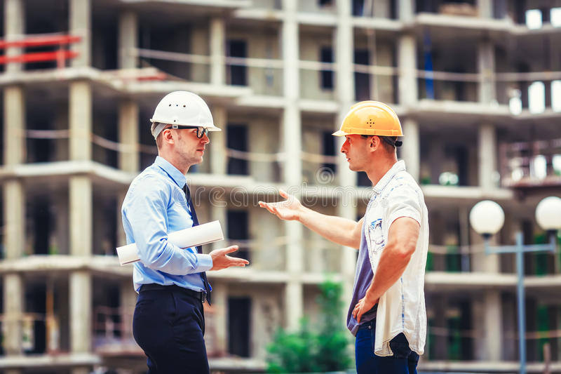 Architect and builder discussing at construction site stock images