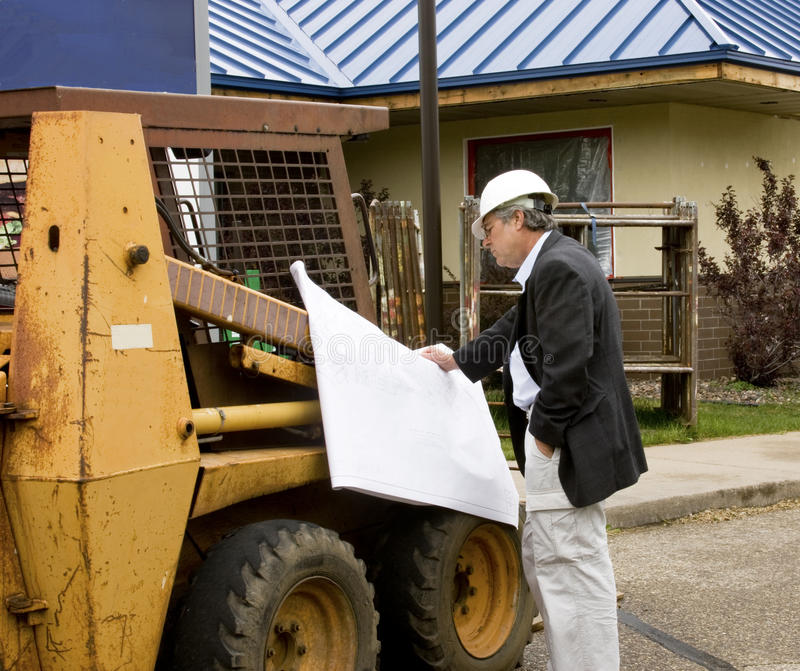 Architect builder reading blueprints. Blueprints being read by architect in suit and white hard hat stock images