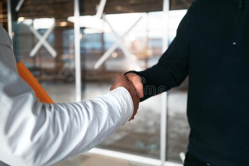 Architect and building engineer have handshake on construction site royalty free stock images