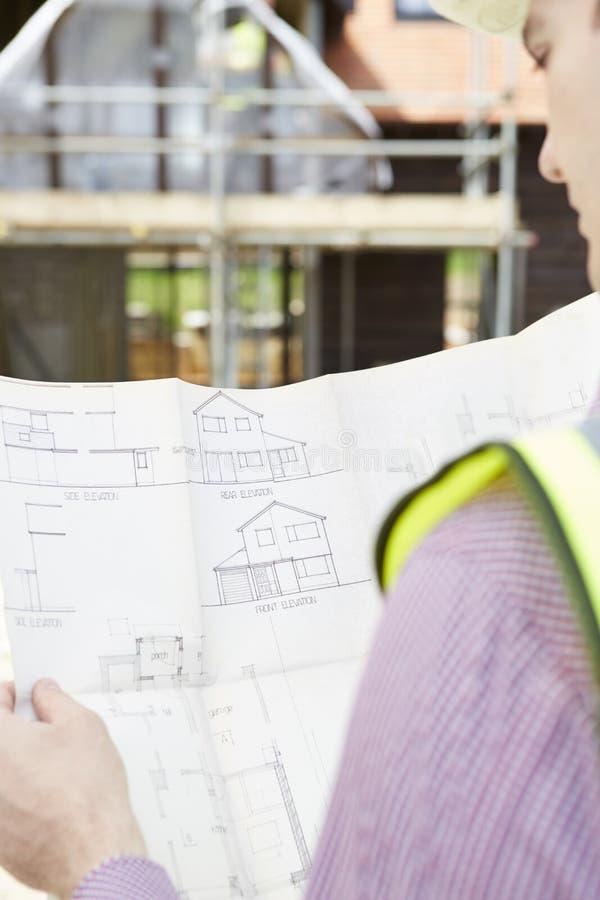 Architect On Building Site die Plannen voor Huis bekijken stock foto