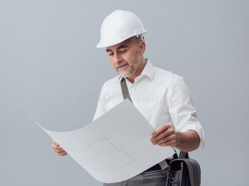 Architect checking a blueprint stock image