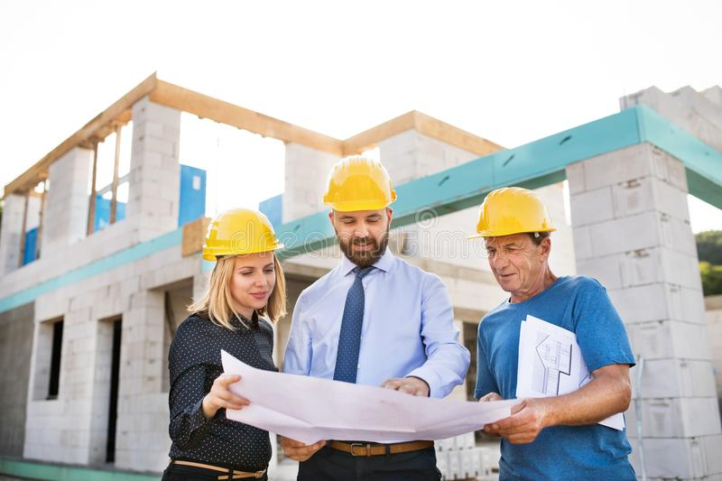 Architects and worker at the construction site. royalty free stock image