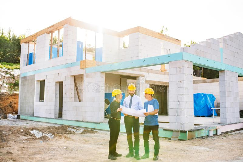 Architects and worker at the construction site. stock image