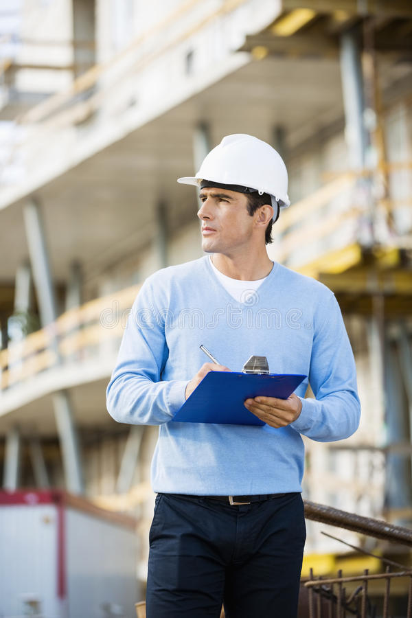 Architect with clipboard and pen working at construction site royalty free stock image