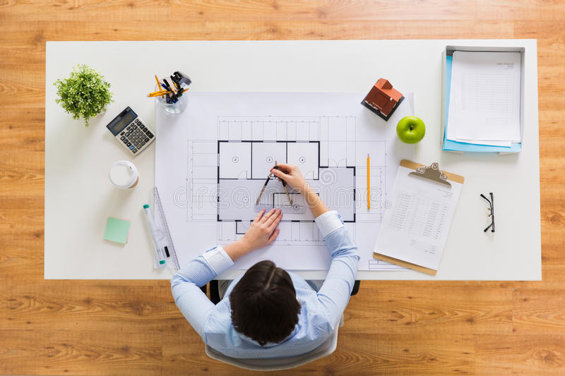 Architect with compass measuring blueprint stock image