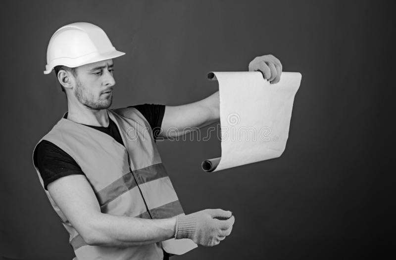 Architect concept. Man in helmet, hard hat holds building plan, controls works, red background. Engineer, architect stock photos