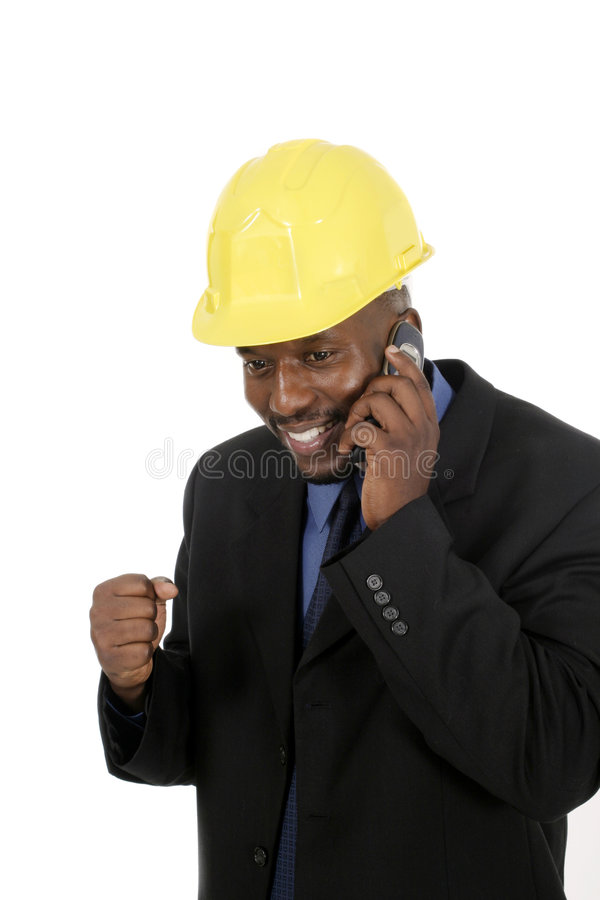 Architect or Construction Contractor. Smiling architect, engineer, or supervisor in yellow hardhat talking on a cellphone stock photography