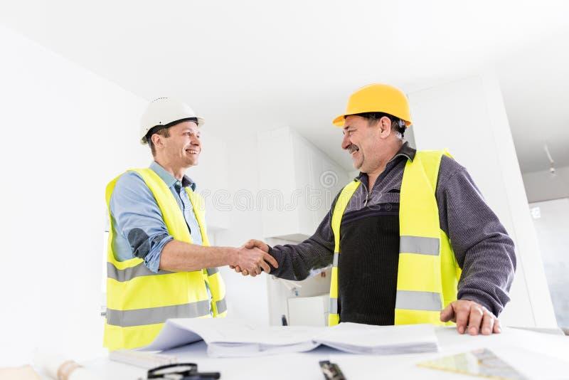 Architect and construction engineer handshake. stock image