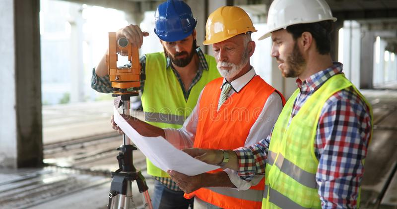 Architect and construction engineer or surveyor discussion plans and blueprints royalty free stock photos