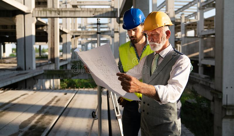 Architect and construction engineer or surveyor discussion plans and blueprints royalty free stock image