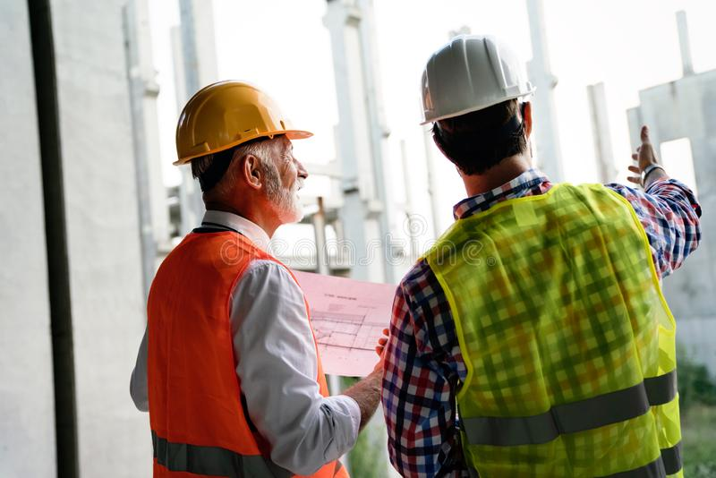 Architect and construction engineer or surveyor discussion plans and blueprints stock photo