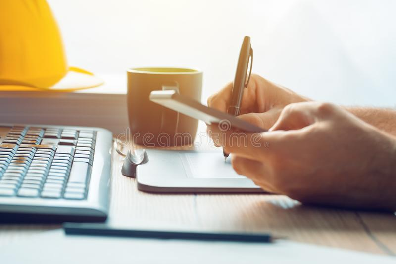 Architect construction engineer working with sketch pen tablet i. N office making a construction project in CAD software, selective focus royalty free stock photo