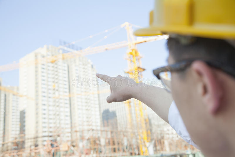 Architect on a construction site pointing at a skyscraper royalty free stock photos