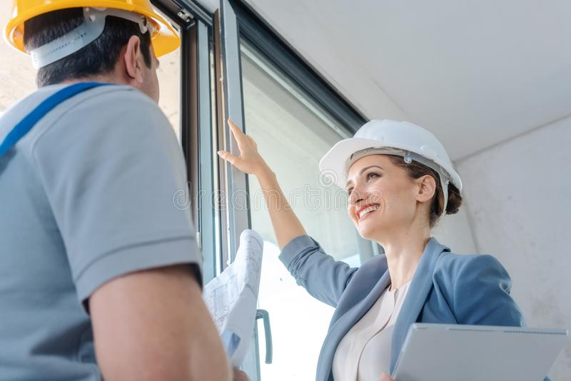 Architect and construction worker checking windows on site stock images