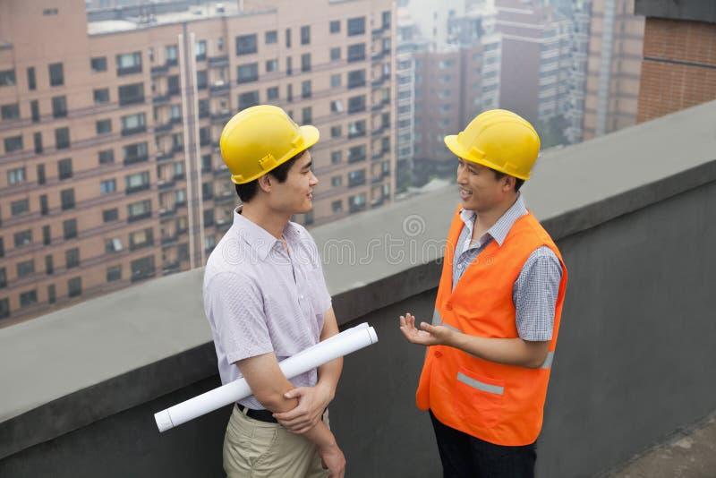 Architect And Construction Worker die op Dak spreken, die blauwdruk, Peking houden royalty-vrije stock fotografie
