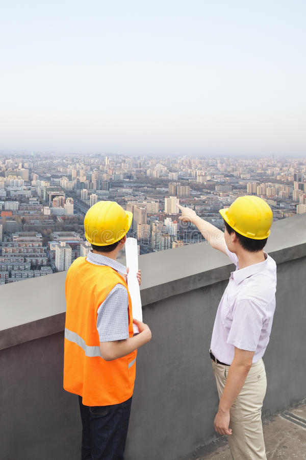 Architect And Construction Worker Talking On Rooftop royalty free stock photography