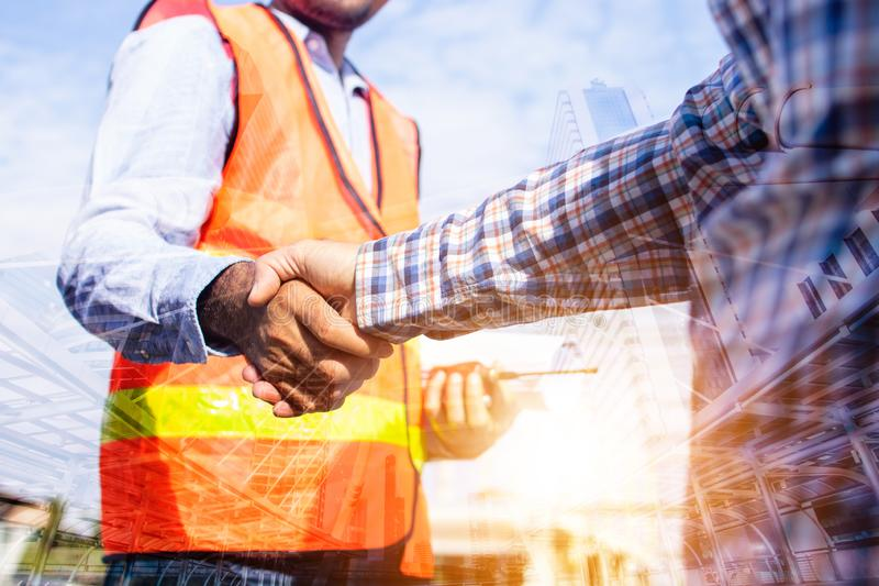 Architect contractor shaking hands with client at construction site royalty free stock image