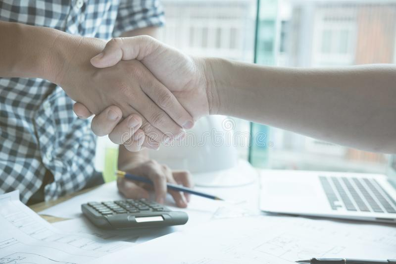 Architect and customer shaking hands at workplace. Engineer hand royalty free stock photos