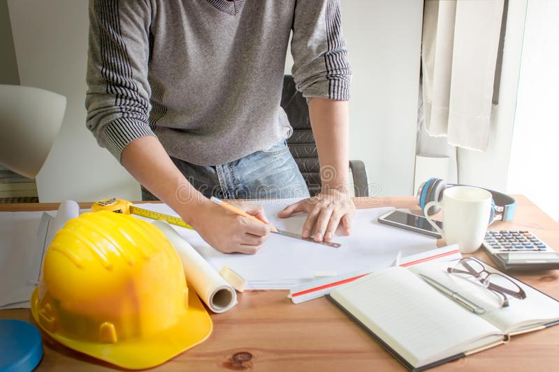 Architect designing on table in office,Vintage,Sunset light,Yellow safety hard hat. With copy space stock photography