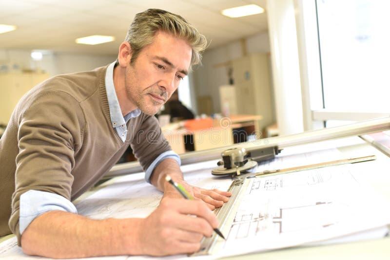 Architect die aan plannen werken stock afbeeldingen