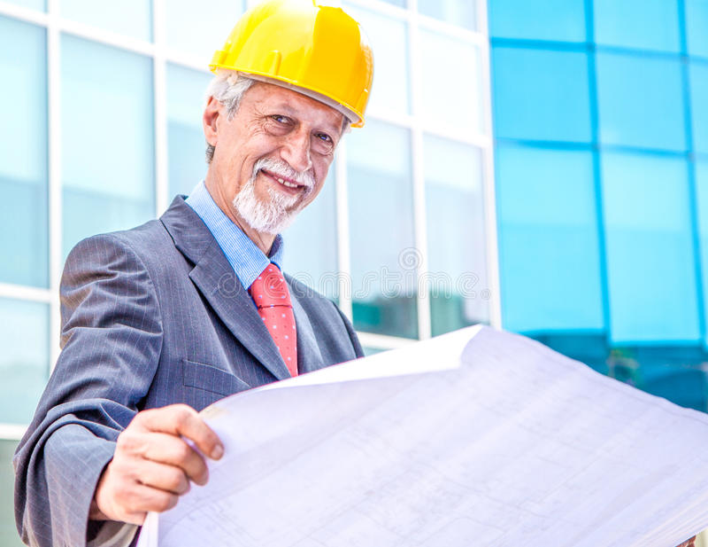 Architect die blauwdruk bekijkt stock afbeelding