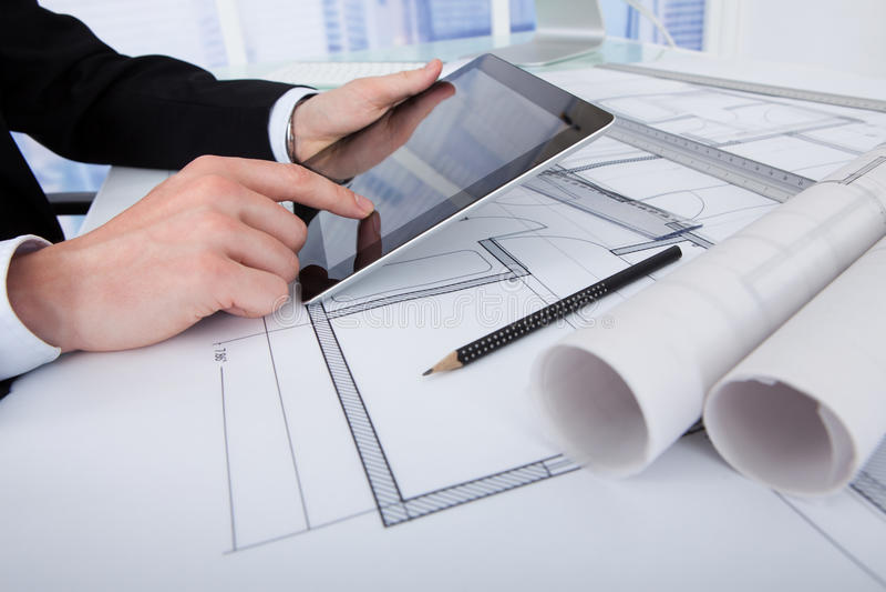 Architect die digitale tablet op blauwdruk in bureau gebruiken stock fotografie